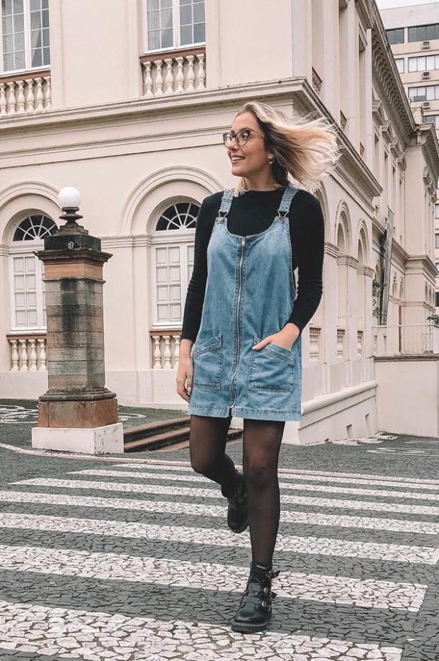 Salopete jeans com meia calça e coturno para o inverno